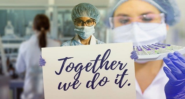 "Doctor during coronavirus holding sign saying ""Together We Do It"""